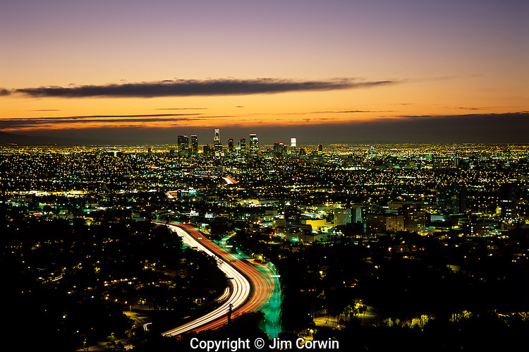 Sunrise over LA with car light streaks on Highway 101 from Mulholland Drive above LA, Los Angeles, California USA