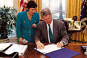 United States President Bill Clinton signs into law S. 1789, legislation that will allow the use of federal bridge funds to seismically upgrade California's highway overpasses so that they can withstand earthquakes in the White House in Washington, DC on March 17, 1994.  The President was joined at the signing in the Oval Office by US Senator Barbra Boxer (Democrat of California) the bill's sponsor.<br /> Credit: White House via CNP