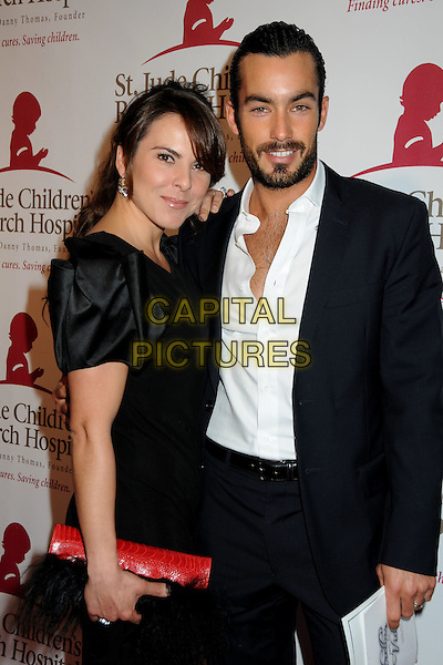 "KATE DEL CASTILLO & AARON DIAZ.St. Jude Children's Research Hospital hosts the ""Estrellas Por La Vida"" Benefit Gala held at Club Nokia LA Live, Los Angeles, California, USA..April 6th, 2010.half length black suit jacket dress white shirt red clutch bag beard facial hair married husband wife.CAP/ADM/BP.©Byron Purvis/AdMedia/Capital Pictures."