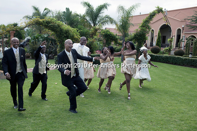 JOHANNESBURG, SOUTH AFRICA - MAY 1: Siphokazi Cola, age 26, and Xolile Ngambane, age 28, dance as they celebrate their wedding day at the Tuscan Wedding village on May 1, 2010, in Johannesburg, South Africa. They dance and show off for the wedding photographer and the relatives outside the Tuscan style reception hall. Newly rich black entrepreneurs, such as this couple, love to throw lavish Western styled white weddings for hundreds of people. This Tuscan wedding themed village venue has a waiting list for two years. The couple went through a traditional and colorful wedding the following day at home. (Photo by Per-Anders Pettersson/Getty Images) (Photo by Per-Anders Pettersson)
