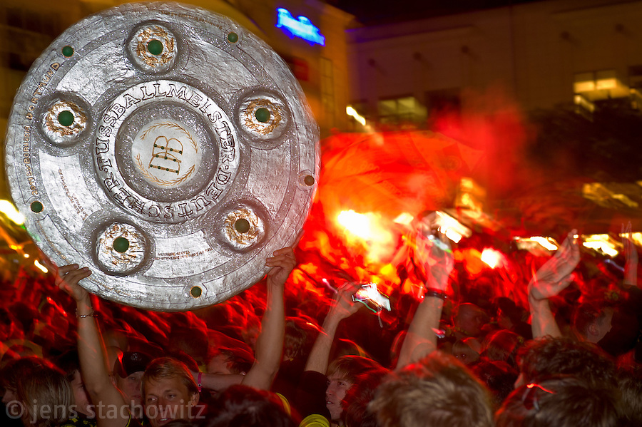 in the ancient marketplace in Dortmund fans celebrate a party because of the title win of their favorite soccer club BVB 09 in the German Premium League. Here they display the replica of the championship shield while bengal fireworks are displayed in the background.
