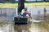 Bill Sandquist paddles past his home in the Red Star District of Cape Girardeau, MO, on Friday, April 29, 2011. A mountain of sandbags and barriers are all that protects the four-year home of Bill and Laura Sandquist. Floodwaters have engulfed the Red Star District of Cape Girardeau in which they live, with the majority of the water rising Wednesday afternoon and Thursday morning, according to Bill Sandquist.