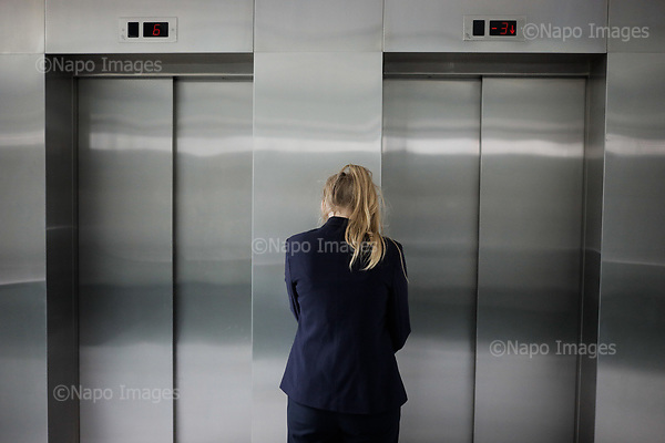 WARSAW, POLAND, JULY 2017:<br /> Office worker standing by the lifts at the Polish foreign affairs ministry.<br /> (Photo by Piotr Malecki / Napo Images)<br /> <br /> WARSZAWA, 7/2017:<br /> Pracowniczka biura stoi przed windami. Ministerstwo Spraw Zagranicznych.<br /> Fot: Piotr Malecki / Napo Images
