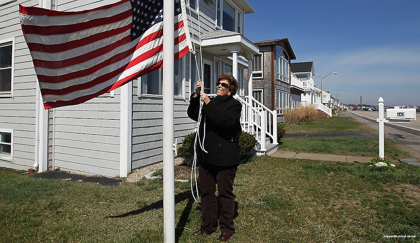 Leigh Cleveland raises her American flag outside her home in Hampton, N.H., Sunday, April 1, 2012.  (Portsmouth Herald Photo Cheryl Senter)