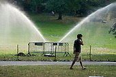 A young man on a mobile phone walks past a water sprinkler in Central Park, Manhattan, New York.
