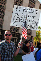 "Phoenix, Arizona. January 19, 2013 - A protester holds a sign to oppose the president proposed changes to gun laws in America. As President Barack Obama proposed new gun regulations last week, gun owners demonstrated against it with national ""Guns Across America"" rallies to defend the Second Amendment. Dozens showed up at the Arizona State Capitol, many of them carrying weapons. Photo by Eduardo Barraza © 2013"
