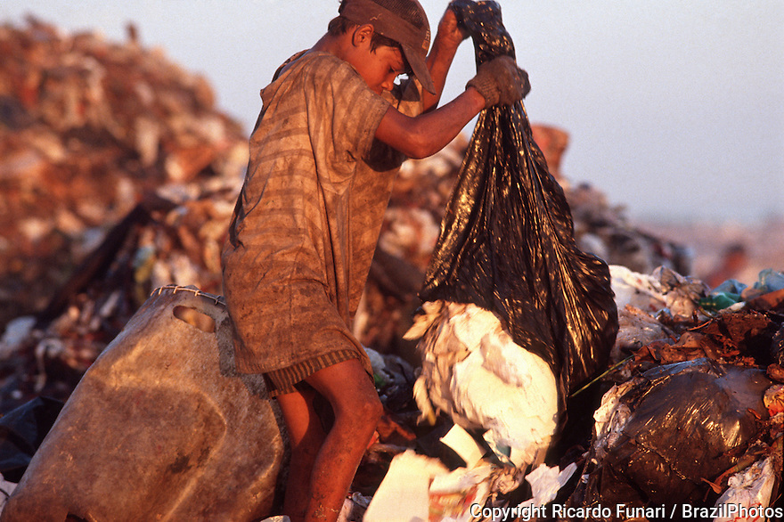 Child labor, pickers sort through garbage finding recyclables as a means of survival at Metropolitan Landfill of Jardim Gramacho (  Aterro Metropolitano de Jardim Gramacho ) in Duque de Caxias city, one of the largest landfills in the world, closed in June 2012 after 34 years of operation when it received most of the garbage produced in Rio de Janeiro city - it was started on an ecologically-sensitive wetland in the 1970s adjacent to Guanabara Bay.