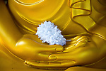 Detail of Buddha statue with offering in palm of  hands, Gangaramaya Temple, Colombo, Sri Lanka,