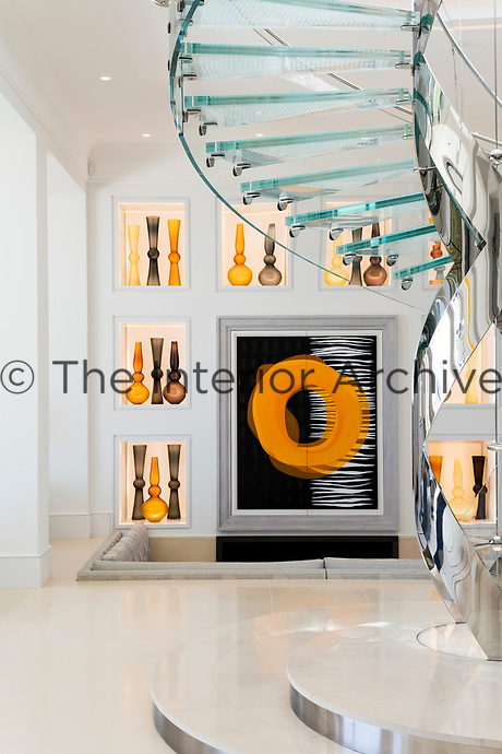 In the spacious entrance hall, a collection of contemporary coloured glassware is displayed in alcoves. The delicate spiral staircase is designed by Eva Jiricna.
