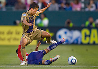 Philadelphia Union defender Shea Salinas (11) leaps over defender Mariano Trujillo (8). The Philadelphia Union and CD Chivas USA played to 1-1 draw at Home Depot Center stadium in Carson, California on Saturday evening July 3, 2010..