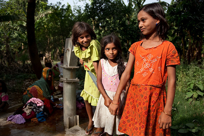 Neha Kumari (5, at right) with Monica Kumari (centre) and Khashbu Kumari  playing at a water pump after a demonstration of oral rehydration salts (ORS) and zinc tablets at a Anganwadi health centre in Pakauli village from which she has benefited. The village located in Vaishali district outside Patna in Bihar, India has been rolling out the ORS and Zinc program as part of the IKEA Social Initiative to combat child mortality rates caused by diarrhea. It is proving to be very successful with education and support provided by local nursing staff, health activists  and program officers from UNICEF. The treatment is a 14 day course administering diluted oral rehydration salts and a zinc tablet which is more effective than salts alone in combating the effects of severe diarrhea. Picture by Graham Crouch/UNICEF