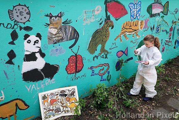 Nederland - Amsterdam - mei 2019.   Kunstenaar Gerti Bierenbroodspot is samen met kinderen van vluchtelingen en buurtkinderen begonnen aan een grote muurschildering in het centrum van Amsterdam. <br /> De schildering van 100 vierkante meter zal verschijnen op de muren van de Leidsedwarstuin, een voorheen verwaarloosd stukje grond aan de Lange Leidsedwarsstraat. Het thema van de muurschildering is de natuur. De kinderen mogen zelf kiezen welk dier ze willen vereeuwigen en worden daarbij geholpen door Bierenbroodspot. De kinderen beschilderen de rechtermuur. Gerti maakt een schildering van enkele etages hoog op de linkermuur. Het project moet over enkele weken af zijn. De gemeente heeft opdracht gegeven voor de muurschildering om toeristen te laten zien dat het Leidsepleingebied een omgeving is waar mensen wonen.      Foto mag niet in negatieve / schadelijke context gepubliceerd worden.    Foto Berlinda van Dam / Hollandse Hoogte