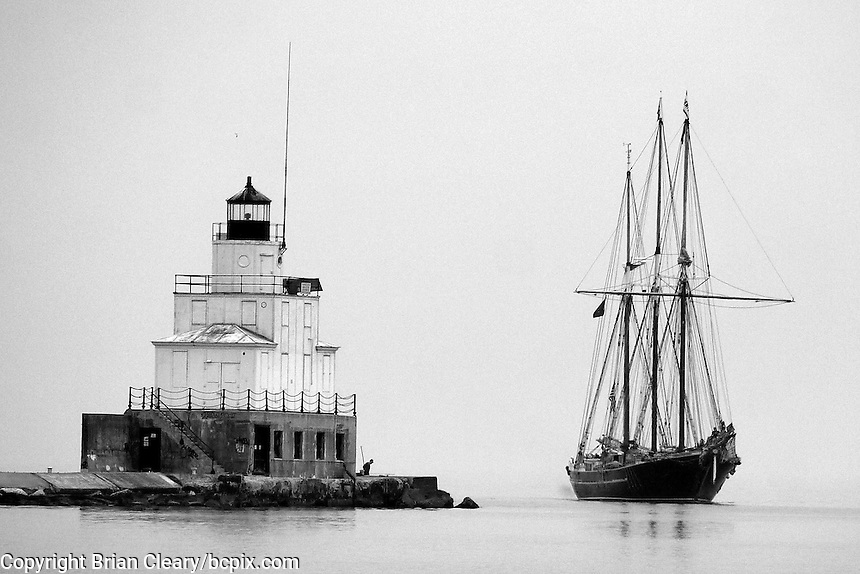 A schooner sails past the lighthouse in Manitowoc, WI, June 24, 2012.  (Photo by Brian Cleary/www.bcpix.com)