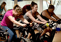 NWA Democrat-Gazette/DAVID GOTTSCHALK Emily Rappe Fisher (center) participates Friday, June 7, 2019, in a Cycle by Color cycle Class at the Jones Center in Springdale. The 30 minute class was taught led by fitness instructor Bobbi Boyd.
