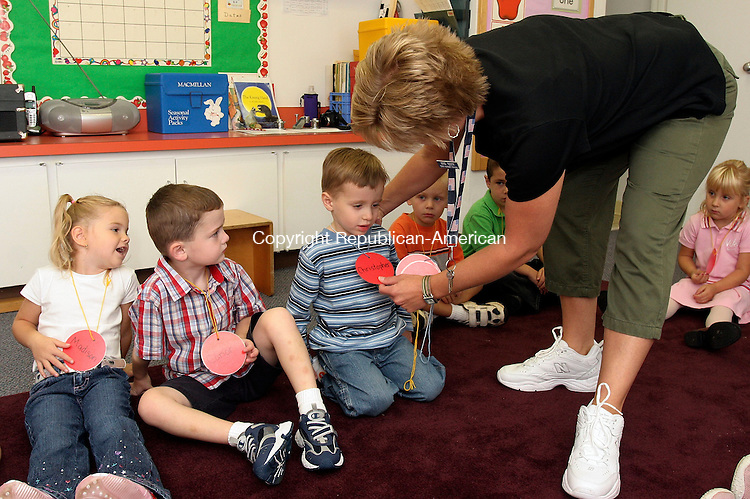 PLYMOUTH, C5-06September 2006-090606TK03- (left to right) At the Terry Nursery School located in the Terryville Congregational Church, area 4 year olds started their first day of school. Madison Maske, Conor Garrity and Christopher DeForest received name tags from Pam Testa, head teacher at the nursery school. The Terry Nursery School is celebrating it's 35th anniversary.  Tom Kabelka Republican-American (Madison Maske, Conor Garrity, Christopher DeForest, Pam Testa)