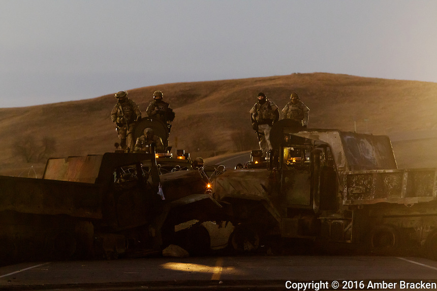 Police stand on top of a barricade, north of pipeline opposition camps and Canon Ball, North Dakota on Monday, November 7, 2016. Government forces are equipped with military type vehicles and equipment.