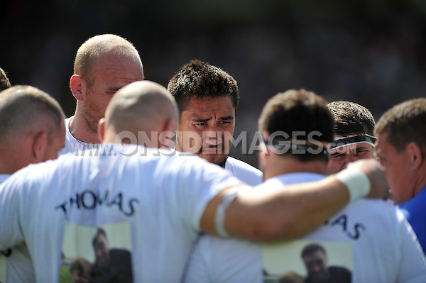 Leroy Houston looks on in a huddle during the pre-match warm-up. Pre-season friendly match, between Bath Rugby and the Scarlets on August 16, 2014 at the Recreation Ground in Bath, England. Photo by: Patrick Khachfe / Onside Images