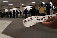 A poll workers hands out stickers to voters at a Columbus, Ohio, early voting center on the first day of early voting in the state.