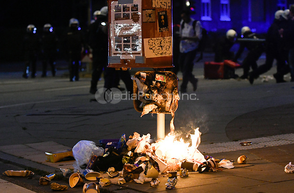 Police in riot gear behind a rubbish bin set alight during demonstrations against the G20 summit in Hamburg, Germany, 7 July 2017. The summit, a meeting of the governments of the twenty largest world economies, begins on the 7 July and concludes on the 8 July. Photo: Axel Heimken/dpa /MediaPunch ***FOR USA ONLY***