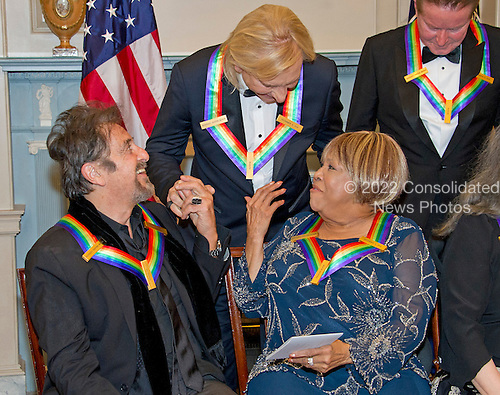 """Al Pacino, left, one of the five recipients of the 39th Annual Kennedy Center Honors, gospel and blues singer Mavis Staples, right, and Joe Walsh of the rock band """"The Eagles,"""" center, congratulate one another as they prepare to pose for a group photo following a dinner hosted by United States Secretary of State John F. Kerry in their honor at the U.S. Department of State in Washington, D.C. on Saturday, December 3, 2016.  The 2016 honorees are: Argentine pianist Martha Argerich; rock band the Eagles; screen and stage actor Al Pacino; gospel and blues singer Mavis Staples; and musician James Taylor.<br /> Credit: Ron Sachs / Pool via CNP"""
