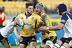Hurricanes' wing Cory Jane, centre, looks to fend off ACT Brumbies' loose forward Ben Mowen, right, in the Super Rugby match at Westpac Stadium, Wellington, New Zealand, Friday, March 07, 2014. Credit: Dean Pemberton