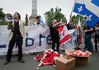 """A man collects Canada flags as RRQ (Reseau de resistance de Quebec - Quebec Resistance network) leader Patrick Bourgeois  speaks during a protest in front of Wolfe's monument on the Plains of Abraham in Quebec city July 1, 2009. The RRQ held their annual protest against Canada by collecting Canada flags to """"send them back to the sender""""."""