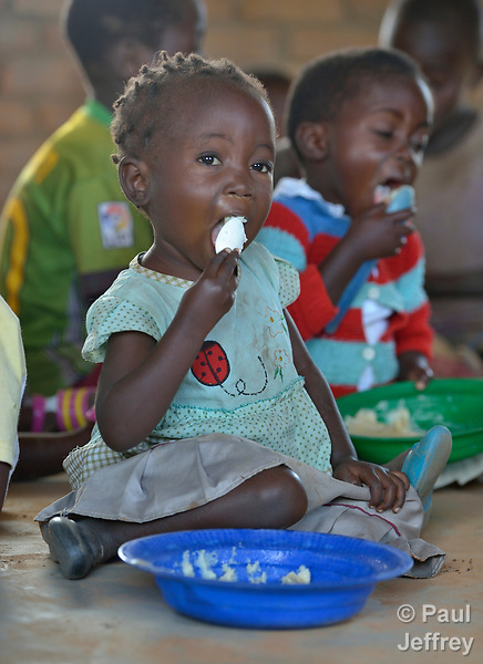 A girl eats a meal in a preschool in Kaluhoro, Malawi. With support from the Ekwendeni Hospital AIDS Program, villagers here participate in a Building Sustainable Livelihoods program, working together to earn and save money, raise more nutritious food, receive vocational training, and better prepare young children for school.