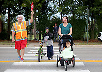 NWA Democrat-Gazette/DAVID GOTTSCHALK Dale Duerr, physical education teacher at Walker Elementary School, helps Wednesday, October 10, 2018, monitor the crosswalk as Becky Nolan walks with her sons Trystan, a third grader, and Ryker, 3, to the school in Springdale.  Walker Elementary School participated in National Walk to School Day. Studies have shown that walking to school positively influences academic achievement, student morning energy levels, attention, truancy, and absenteeism.
