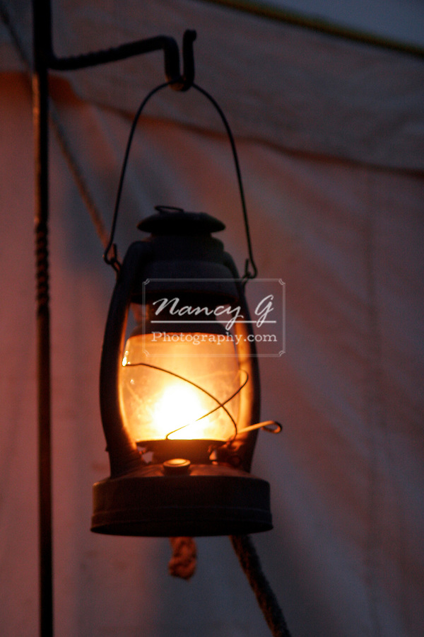 An 1850s Oil Lantern hanging on a metal staff outside of a tent at a western reenactment