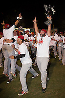 Joe Filomeno (31) of the Hickory Crawdads holds the Championship trophy as he and his teammates celebrate after defeating the Asheville Tourists 5-1 to sweep the South Atlantic League Championship at McCormick Field on September 17, 2015 in Asheville, North Carolina. (Brian Westerholt/Four Seam Images)