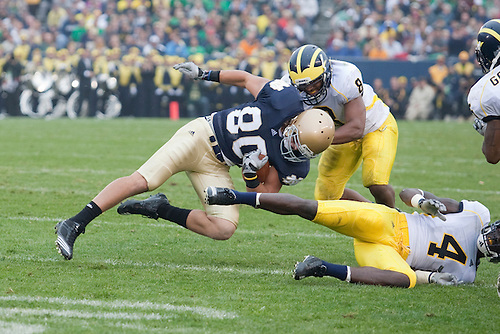 Michigan linebacker Jonas Mouton (#8) tackles Notre Dame tight end Tyler Eifert (#80) during NCAA football game between the Notre Dame Fighting Irish and the Michigan Wolverines.  Michigan defeated Notre Dame 28-24 in game at Notre Dame Stadium in South Bend, Indiana.