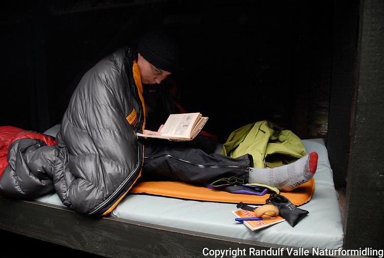 Jente leser bok, innpakket i sovepose ---- Girl reading