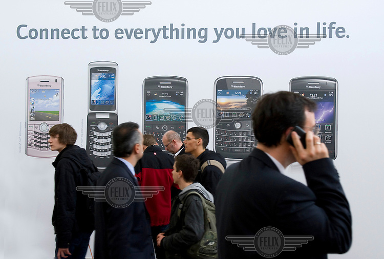 Visitors walk past an exhibit which displays Blackberry hand held devices at the Computer Fair Cebit 2009 in Hanover.