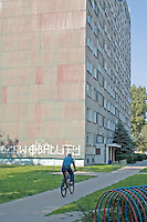 Bicycler traveling by Bloc housing a painful reminder of the Communist era. Balucki District Lodz Central Poland