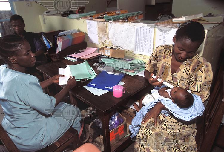 ©Caroline Penn/Panos Pictures..Kenya, Kilifi. Support staff Esther feeds abndonned child.