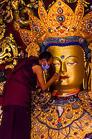 A monk touches up paint on a statue of Buddha, Samye Monastery, Chatang, Lhoka (Shannan) Prefecture, Tibet (Xizang), China. Samye is the first Buddhist monastery built in Tibet.