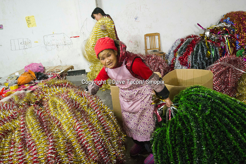 November 28, 2015, Yiwu, China - Grandma Wang, 65 at work in the Xin Shua tinsel factory. She works in tandem with her daughter in law Wang Huimei, 22. They are both from Yunnan and are paid by each bunch of tinsel they pack into cardboard boxes. The factory makes around 30 million RMB (GPB 3.12) of tinsel each year.Photo by Dave Tacon / Sinopix