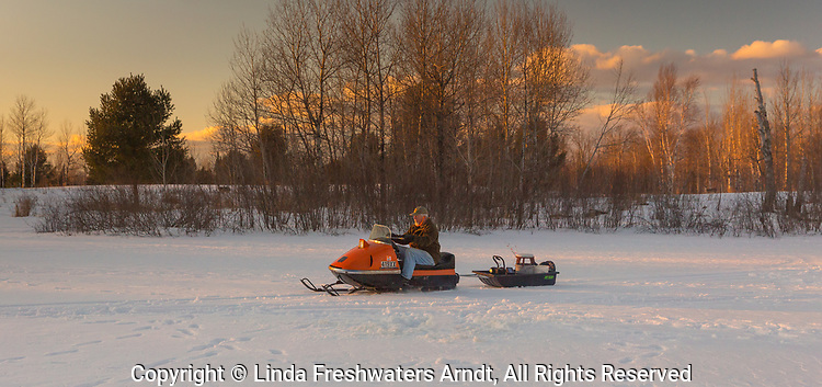 Ice fisherman driving a vintage 1970 AMF Mark V 400 Ski-Daddler snowmobile.