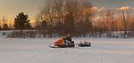 Ice fisherman driving a vintage 1970 AMF Mark V 400 Ski-Daddler snowmobile.