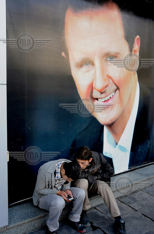Two young men trying out their mobile phones outside the offices mobile phone company Syriatel where portraits of president Bashar al-Assad adorn the window's blinds.