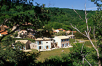 The hamlet of newly built houses is located against a wooded hillside