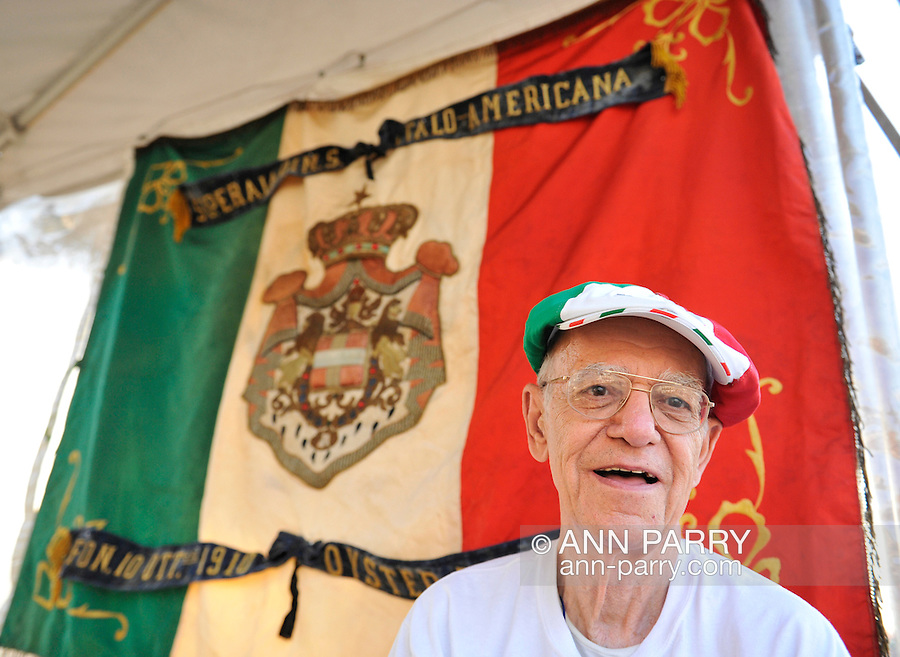 At the Feast of St. Rocco on July 14, 2012, in Oyster Bay, New York, USA, a member of the Italian American Citizens Club is next to its banner. This Oyster Bay club organized the five-day festival, which ends July 15, to promote Italian-American heritage. The festival has been a Long Island tradiation for over 100 years.