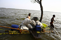 People transport all they can on a homemade raft. Thousands of people were displaced in Shyamnagar Upazila, Satkhira district after Cyclone Aila struck Bangladesh on 25/05/2009, triggering tidal surges and floods..