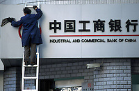 A worker cleans a sign at a branch of the Industrial and Commercial Bank of China in Shanghai, China..