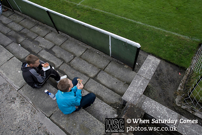 Pollok 2 Neilston Juniors 1, 13/08/2008. Newlandsfield, Sectional League Cup. Two young spectators eating pies on the terracing while watching Pollok (black-and-white) taking on local rivals Neilston Juniors in a Sectional League Cup (Central) Section 5 tie at Newlandsfield on Glasgow's south side. The home side won the game by 2-1 in front of 302 fans. Junior football was divided into East, West and North sections and played throughout Scotland. It had its own governing body, the SJFA and regional pyramid structure and national cup competition. Photo by Colin McPherson.