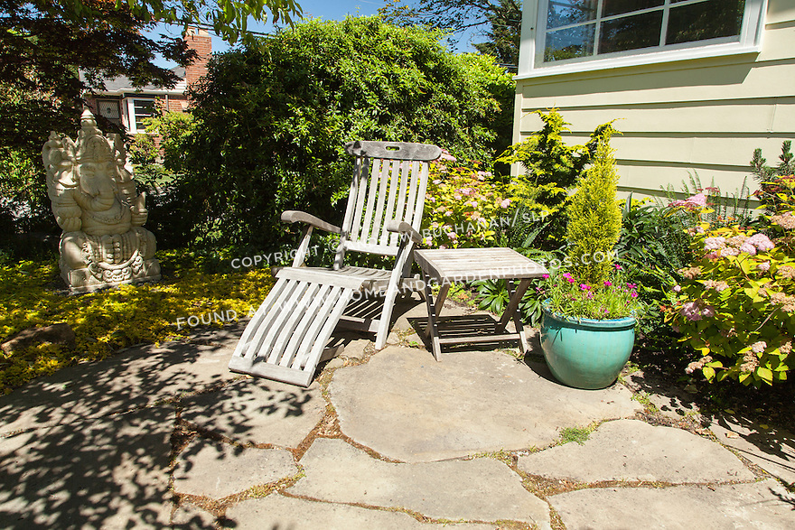 A wooden lounge chair on a small flagstone patio offers a place to relax.