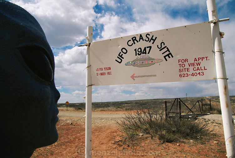 UFO crash site. An alien face examines sign advertising the site where wreckage of a UFO was found on the Brazel ranch near Roswell, New Mexico, USA. It was near Roswell on the evening of 2 July 1947 that many UFO sightings were reported during a thunderstorm. Next morning a rancher, Mac Brazel, discovered strange wreckage in a field. When the impact site was located, a UFO craft and alien bodies were allegedly found. On 8 July 1947, the Roswell Daily Record announced the capture of a flying saucer. The official explanation was that it was a crashed weather balloon. Many Roswell inhabitants, however, believe this a cover up, and Roswell has become a symbol for UFO enthusiasts. Photo illustration. (1997) .