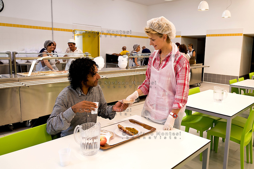 """ROME, ITALY - SEPTEMBER 24: A guest and a voluntary during the dinner the refectory at the hostel  """"Don Luigi Di Liegro"""" of the Caritas of Rome in Via Marsala, Rome. The new facility of 500 for the evening canteen and 300 beds to the hostel,  hosts marginalized people. The hostel opened in 1987 has been renovated to make it more efficient, the social reintegration of the guests  on September 24, 2016 in Rome, Italy."""