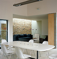 The dining area of this open-plan living space is furnished with an Eames table and contemporary chairs originally designed for office use