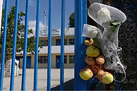 "Pictured: Flowers and tributes left at the gate of the 6th primary School in Acharnes, Athens, Greece. Saturday 10 June 2017<br /> Re: An 11 year old boy has been shot dead by a ""stray bullet"" during a school celebration in Acharnes (Menidi) area, in the outskirts of Athens, Greece.<br /> Marios Dimitrios Souloukos ""complained to his mum"" who works as a teacher at the 6th Primary School of Acharnes that he was feeling unwell, he then collapsed with blood pouring out from the top of his head.<br /> His mum tried to revive him assisted by other teachers while his schoolmates who were reportedly upset, were hurriedly removed by their parents.<br /> According to locals an ambulance arrived 25 minutes late.<br /> Hundreds of police officers have been deployed in the area and have raided many properties.<br /> Shells matching the fatal bullet which hit the boy on the top of his head were found in a house yard nearby.<br /> Local people reported hearing shots being fired at a nearby Romany Gypsy camp before the fatal incident.<br /> The area has been plagued with criminality during the last few years."